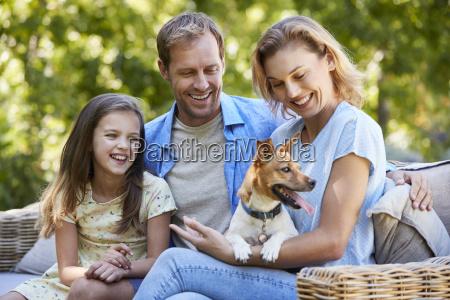 eltern und tochter sitzen mit hund
