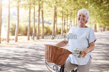 portraet von laechelnder senior frau radfahren