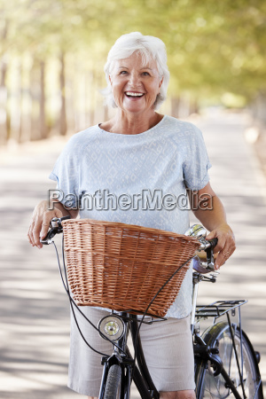 portrait of smiling senior woman cycling