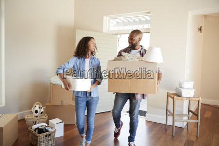 couple carrying boxes into new home