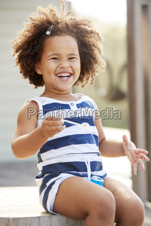 young black girl blowing bubbles outside