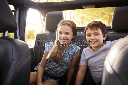 children sitting in back seat of