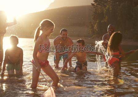familie mit freunden die den abendschwimmen