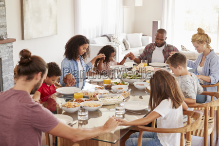 two families praying before enjoying meal