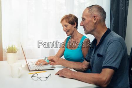 senior couple using laptop for internet