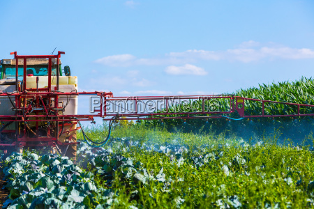 traktor besprueht feld mit chemikalien