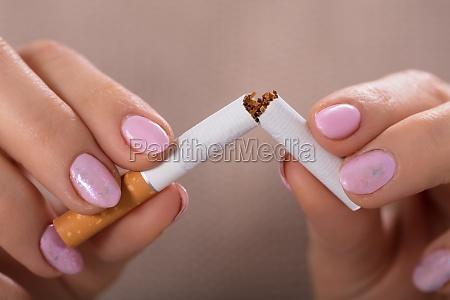 woman holding zerbrochene cigarette