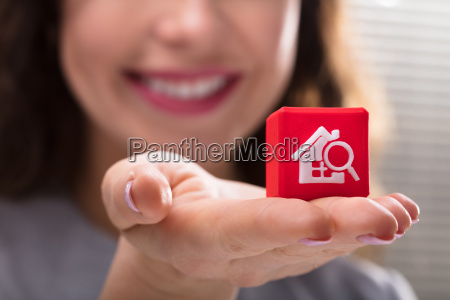 woman holding cubic block with home