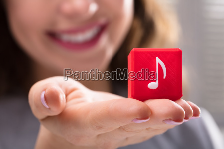 woman holding cubic block with music