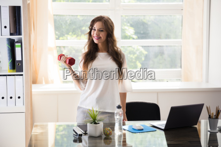 businesswoman exercising with dumbbells