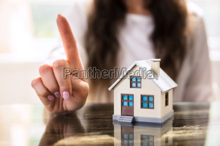 businesswoman gesturing no sign near house