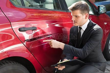 man filling insurance form near damaged