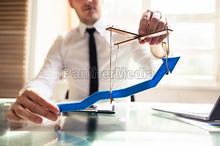 businessperson manipuliert blauen pfeil