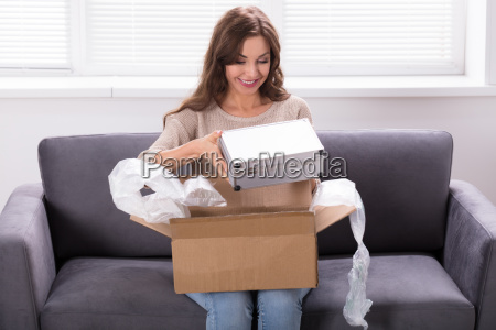 woman looking at product delivered from