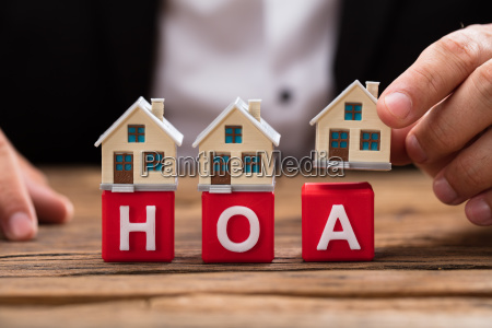 businessperson placing house model over hoa