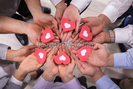 businesspeople holding red hearts