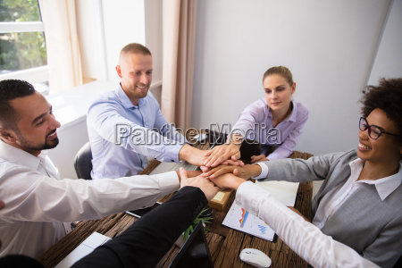 young businesspeople stacking hands