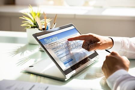 geschaeftsmann fuellt online umfrageformular auf laptop