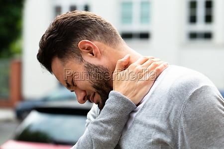 mann erfleckte von nackenschmerzen
