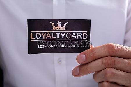 businessman holding loyalty card