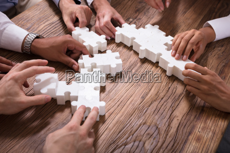 businesspeople solving jigsaw puzzle together