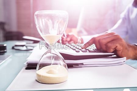 hourglass vor geschaeftsperson berechnung rechnung