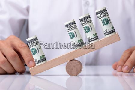 menschliche hand die unwucht zwischen banknoten