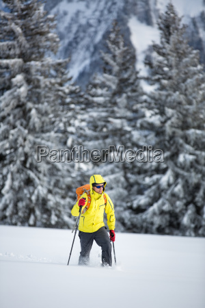 young man snowshoeing in high mountains