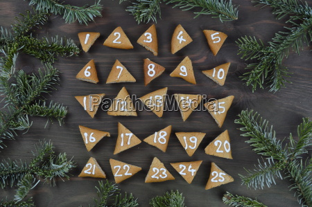 25 nummerierte adventskekse auf braunem holz