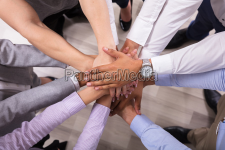 elevated view of businesspeople stacking hands