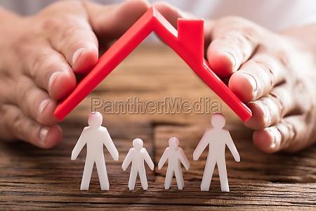 person schuetzt familienfiguren mit dach