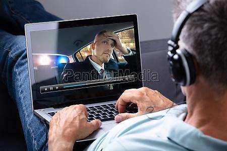 entspannter mann schaut video auf laptop