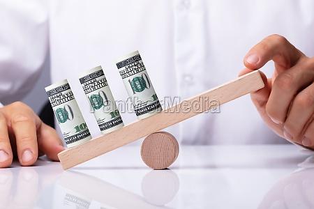 person balancieren geldscheine auf seesaw