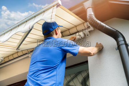 man installing awning on house facade