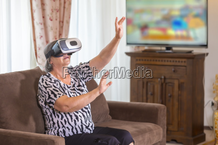AEltere frau mit dem virtuellen kopfhoerer