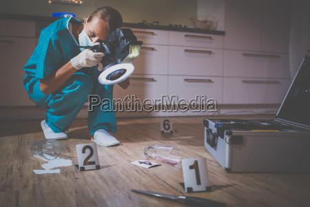forensischer spezialist im schutzanzug der fotos