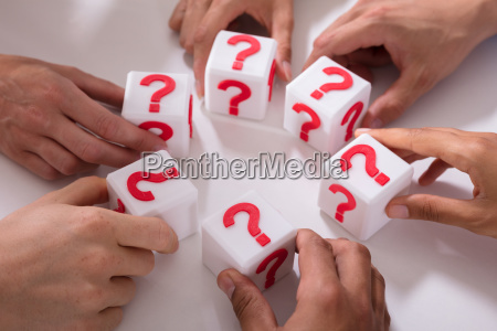 businesspeople holding cubic blocks with question