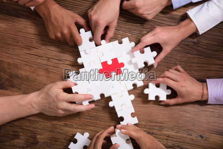 elevated view of businesspeople solving jigsaw