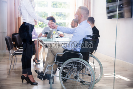 disabled businessman shaking hand with his