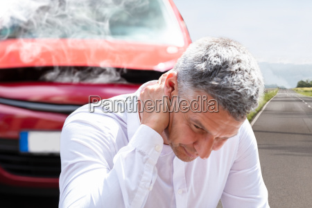 man suffering from neck pain in