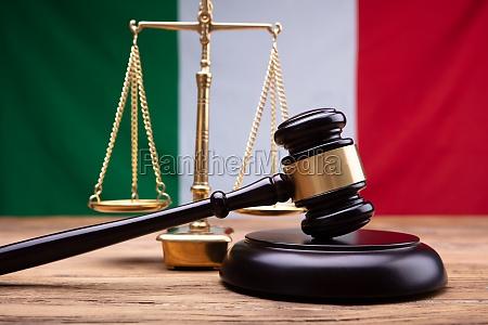 italienische flagge hinter gerechtigkeits skala und