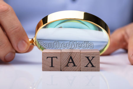 person holding magnifying glass over tax