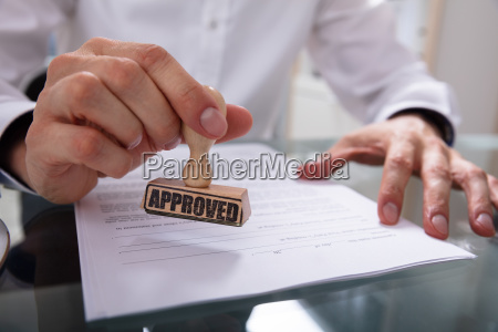 businessman stamping approved on contract paper