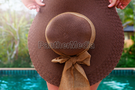 woman with sunhat in tropical resort