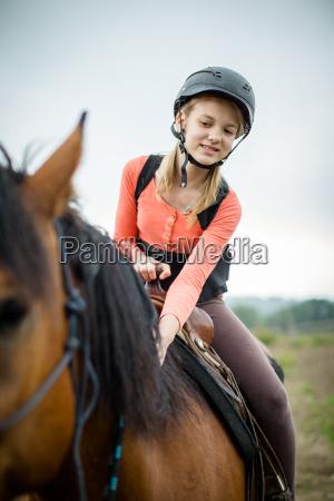 niedliches junges maedchen reitet ein pferd