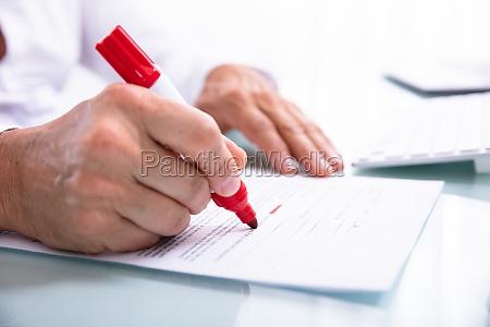 businessperson marking error with marker on