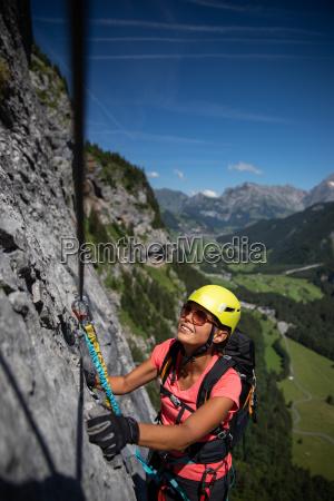 huebsche kletterinnen auf einem klettersteig klettern