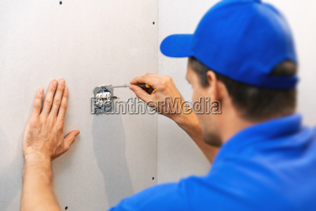 electrician installing electrical outlet on the