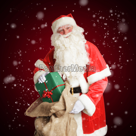 laechelnder weihnachtsmann holt geschenke in seine