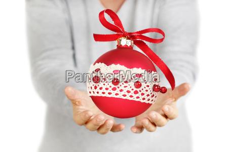 frauenhaende die roten weihnachtsball lokalisiert auf